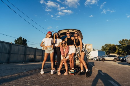 Five young women have fun at the car park. Stock Photo