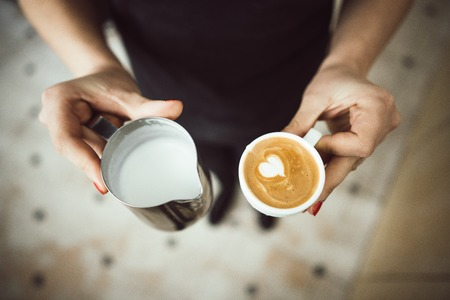 Barista holds two cups, with milk and latte Stok Fotoğraf - 114395678