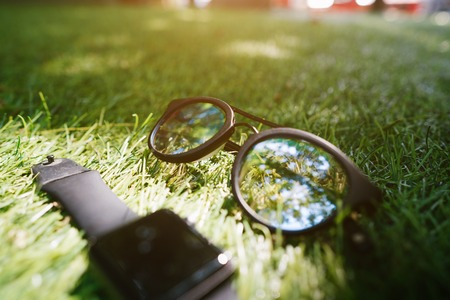 Smart watch and sunglasses lie on the grass