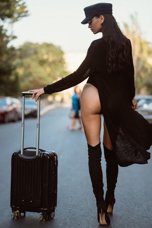 Une jeune femme dans un justaucorps noir posant sur un appareil photo