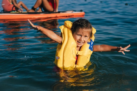 Little girl in a life jacket bathe in the sea. Stock Photo