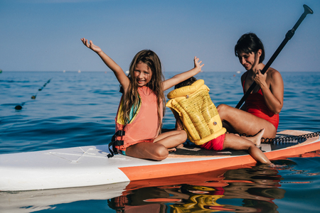 Mother with two daughters on a paddle board