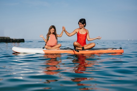 Mom and little daughter doing yoga on the paddle board Standard-Bild