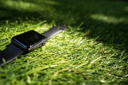 Smart watch lie on the green grass