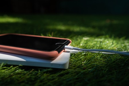 The smartphone is charging from powerbank on the grass