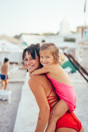 Young mother giving daughter piggyback ride on the beach