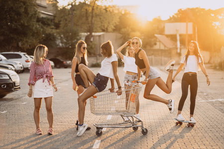 Young women with a supermarket cart have fun