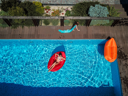 Mom and her daughter rest on the pool. Reklamní fotografie - 116019400