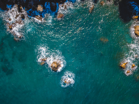 Drone top view of a sea cliff and a beach