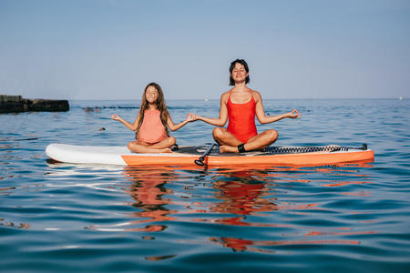 Mom and little daughter doing yoga on the paddle board Stock Photo