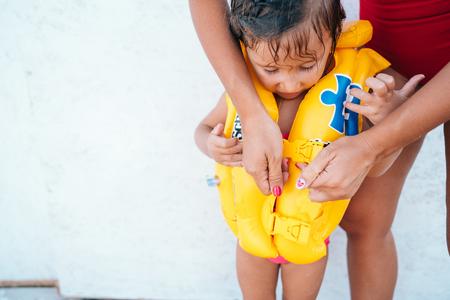 Eine Mutter hilft ihrer Tochter mit ihrer Schwimmweste Standard-Bild