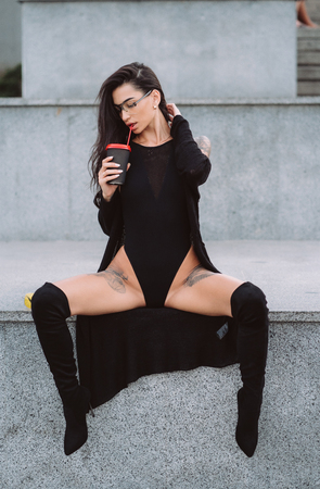 Woman in a sexy position is drinking street coffee.