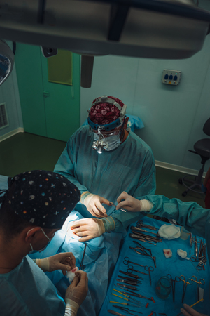 Surgeon and his assistant performing cosmetic surgery on nose Imagens