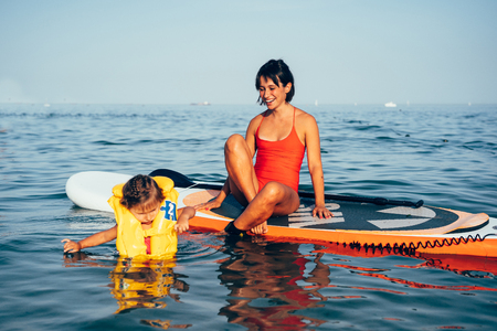 Mother with daughter on a paddle board Imagens