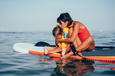 Mother with daughter on a paddle board Banco de Imagens