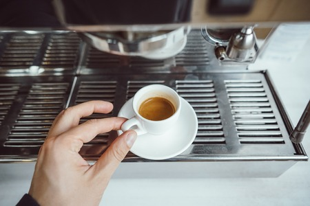 close-up view of glass cup with cappuccino and coffee machine Stock Photo