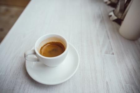 Cup of cappuccino on the white wooden table.