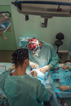 Surgeon and his assistant performing cosmetic surgery on nose Reklamní fotografie