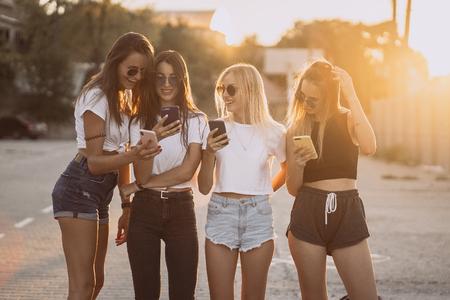Cztery atrakcyjne kobiety stoją na parkingu ze smartfonami