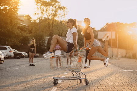 Friends ride on carts, near the supermarket Banque d'images