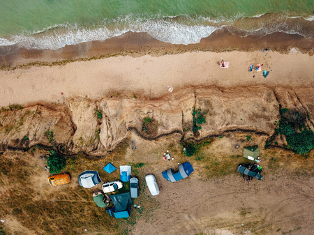 People rest on the wild beach with their families.