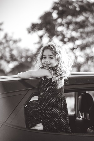 A little girl is standing on the door of the car