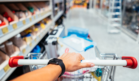 Human Hand Close Up With Shopping Cart in a Supermarket Walking Trough the Aisle Reklamní fotografie
