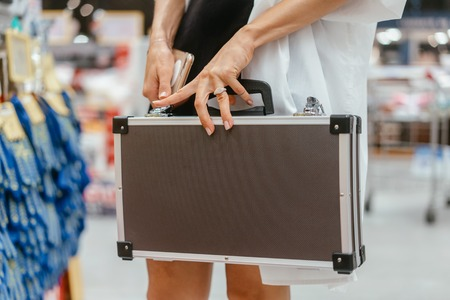 The girl holds a small aluminum case in supermarket blur background Reklamní fotografie