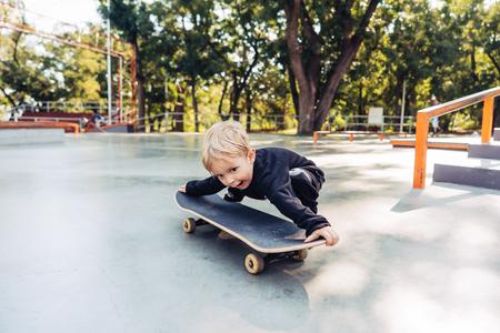 Little boy trying to pick up a skateboard Фото со стока