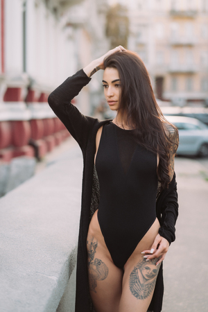 Sexy, young woman in leotard posing on camera in the streets Stockfoto