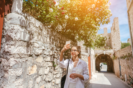 Young girl walking through ancient narrow streets and takes a picture