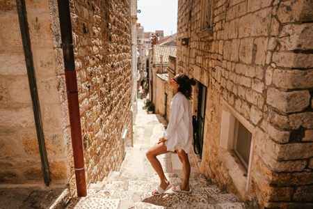 Young girl walking through ancient narrow streets on a beautiful summer day Stock fotó - 119696391