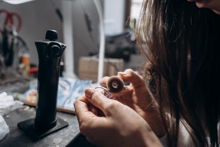 The master processes the valuable metal in the home workshop Reklamní fotografie