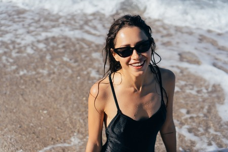Beautiful young woman in black wet swimsuit