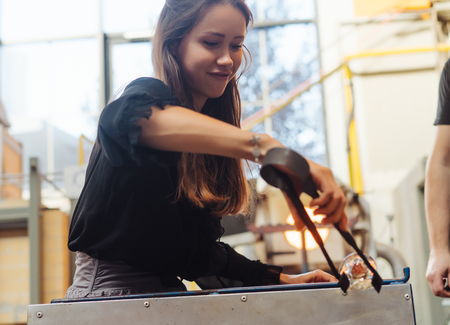 A glassblower student tries to make a flower out of glass