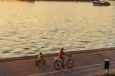 Mom and son ride bikes along the promenade Imagens