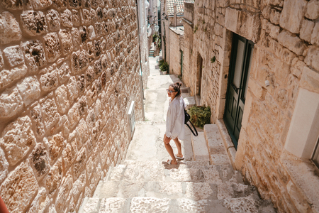 Young girl walking through ancient narrow streets on a beautiful summer day Фото со стока - 119520091
