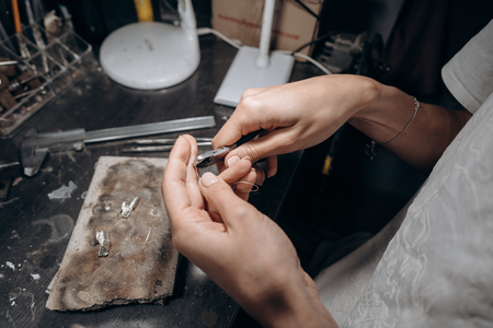 Woman jeweler cuts off a piece of solder with nippers 스톡 콘텐츠