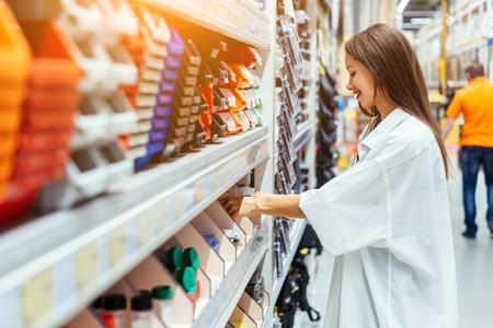 La donna sceglie scatole di plastica di diversi colori per l'officina