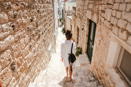 Young girl walking through ancient narrow streets on a beautiful summer day in Croatia south Europe
