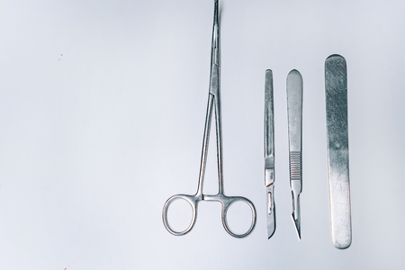 Scapula for throat, two scalpels and clamp on a light background Foto de archivo - 119995727
