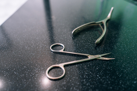 surgical scissors and spreader lie on the table