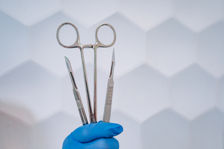 A rubber gloved hand holds two scalpels and a clamp Stock Photo