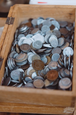 Old coins of different denominations are in a small wooden box Stockfoto