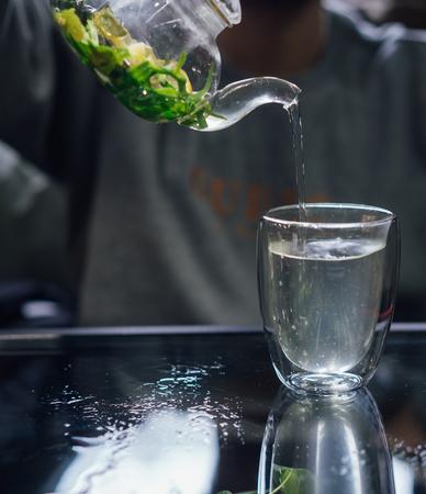 Hot green tea with mint, steam rises, dark background