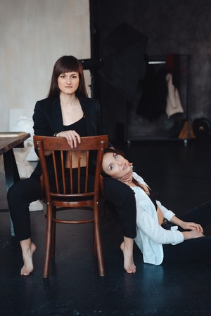 two girls are posing for the camera, one sitting on a chair, other on the floor