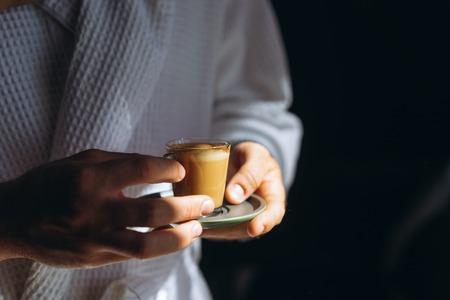 A man in a bathrobe is holding a small mug of coffee