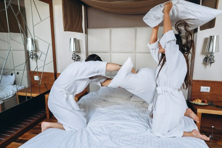 Cheerful couple have fun in the bedroom fighting with big pillows at home