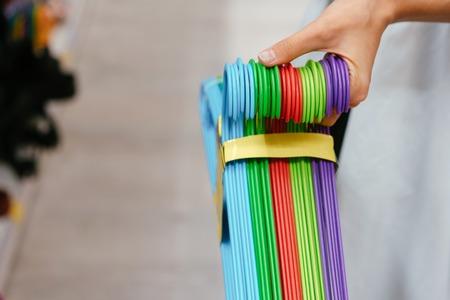 Weibliche Hand, die eine Reihe von Kleiderbügeln hält Standard-Bild