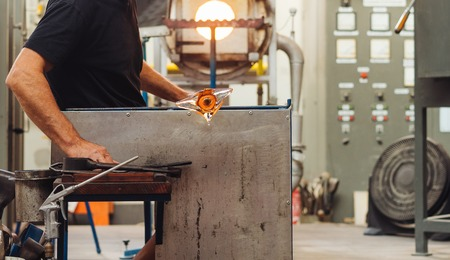A Glass Blower Shaping Molten Glass into a Piece of Art Stock Photo